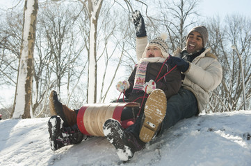 Father and daughter sledding down snow covered hill