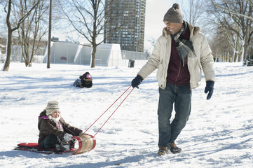 Father pulling daughter on sled