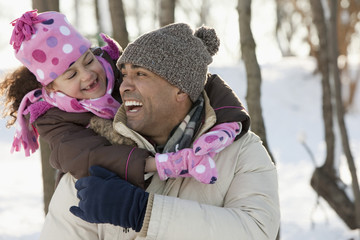 Daughter hugging father in snow