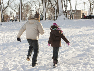Father and daughter walking through snow