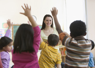 Students raising hands in classroom