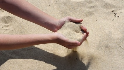 Hands full of sand falling through the fingers