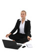 Businesswoman practicing yoga in front of her laptop