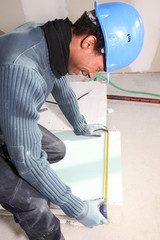 Man measuring plasterboard