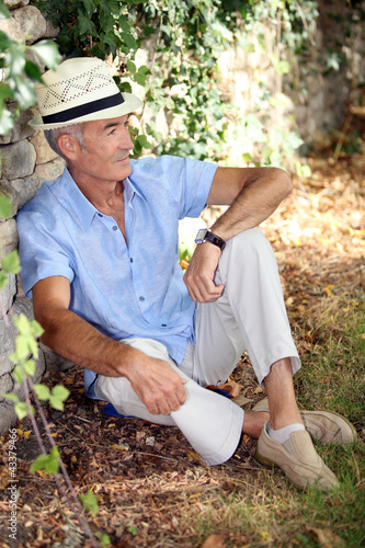 Mature man resting along a wall.