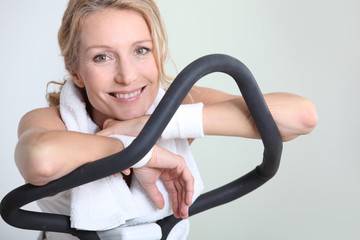 Woman resting for a moment on an exercise machine