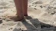 Bare foot on the sand beach makes a hole