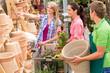 Garden center salesman selling pot to customer