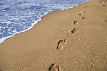 Orme di un uomo che passeggia sulla spiaggia in riva al mare