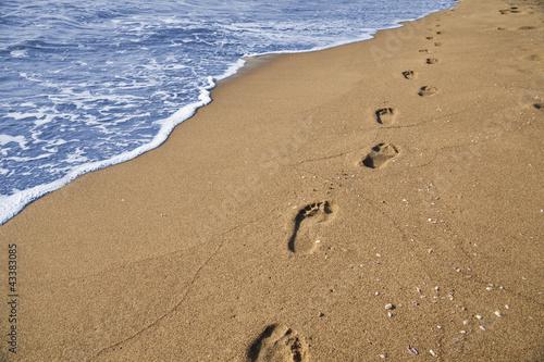 canvas print picture Orme di un uomo che passeggia sulla spiaggia in riva al mare