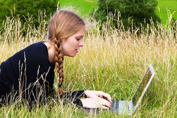 Junge Frau mit Laptop auf der Wiese
