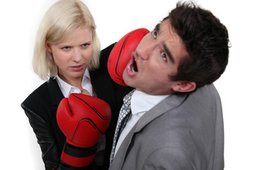 businesswoman hitting a colleague with a boxing glove