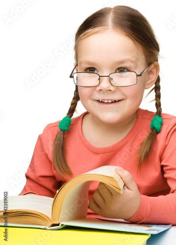 Cute cheerful little girl reading book