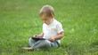 Baby boy working with Tablet PC sitting on the grass
