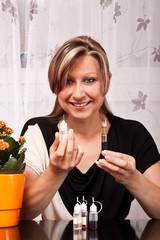 Junge blonde Frau präsentiert Utensilien für elektrische Zigar