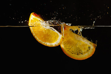 Segments of fresh orange falling into the water with a splash