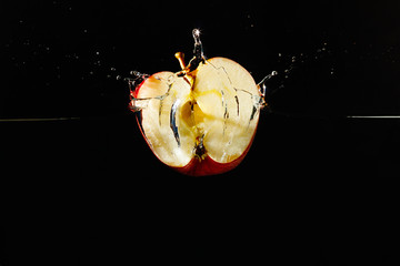 Halved apple falling into the water with a splash