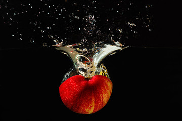 Halved red apple falling into the water with a splash