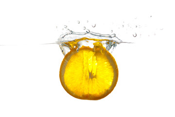 Sliced lemon falling into the water with a splash