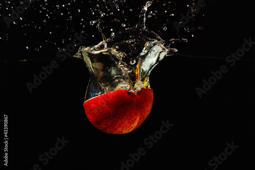 Halved fresh apple falling into the water with a splash