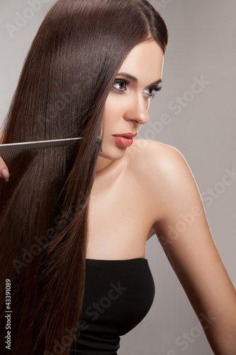 Beautiful Woman combs her Healthy Long Hair. High quality image.