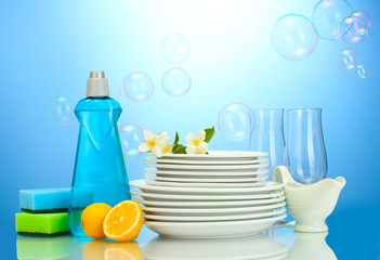 empty clean plates and glasses with dishwashing liquid, sponges