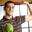 Cheerful man with cabbage, showing biceps