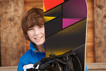 Boy With Snowboard On Ski Holiday In Front Of Wooden Background