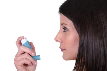 Woman using her inhaler
