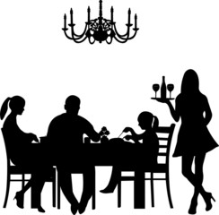 Silhouette of a restaurant  were a family enjoy their dinner