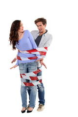 Couple being forcibly held together by caution tape