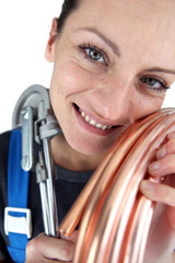 Woman with copper pipe and bending tool
