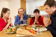Teenage Family Saying Grace Before Eating Lunch Together In Kitc
