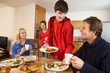 Helpful Teenage Children Serving Food To Parents In Kitchen