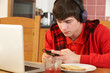 Teenage Boy Using Laptop And Listening To MP3 Player Whilst Eati