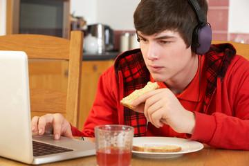 Teenage Boy Using Laptop Whilst Eating Breakfast