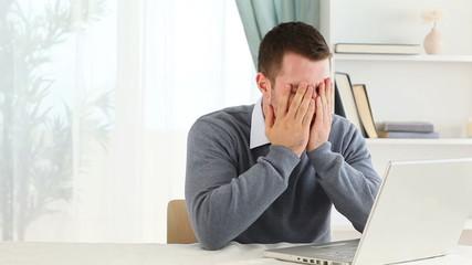 Depressed man working on a laptop