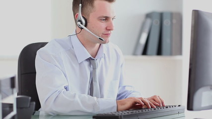 Businessman typing at computer while speaking with headset