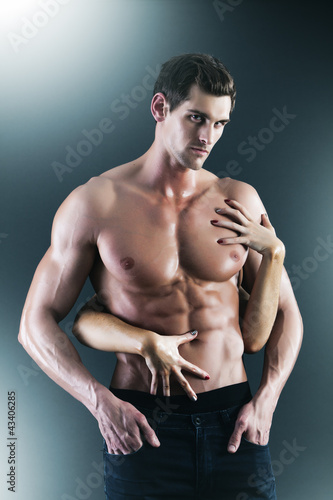Sexy muscular naked man and female hands