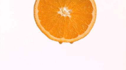 Drop of orange juice in super slow motion falling