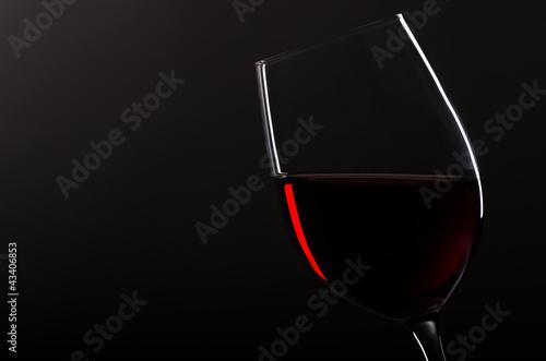 Weinglas mit Rotwein vor schwarzem Hintergrund