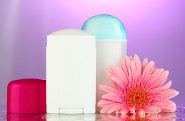 deodorant botttles with flower on purple background