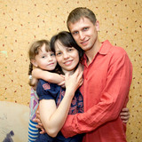 Father, mother and daughter hugging and smiling