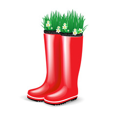 red rubber boots with grass and flowers blooming