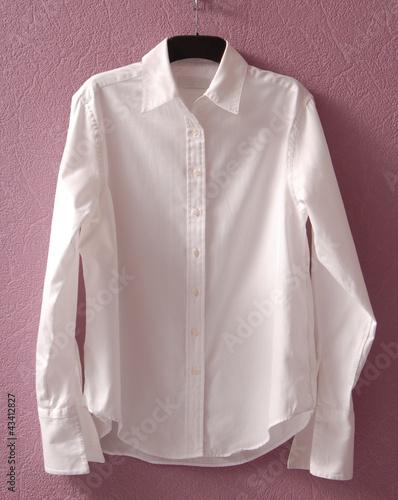 Белая женская рубашка на вешалке.