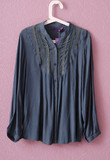 Синяя, шелковая блузка на вешалке.