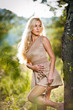 sensual young blonde female on field in sexy short brown dress