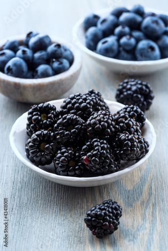 Blackberries and blueberries in small bowls