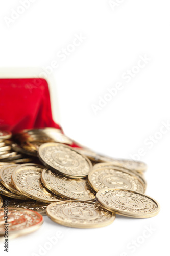 Scattered gold coins are in hot red partly viewed purse