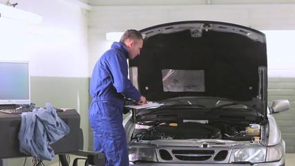 Car mechanic checking an engine